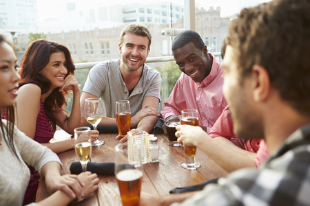 horizontal bar: Group Of Friends Enjoying Drink At Outdoor Rooftop Bar