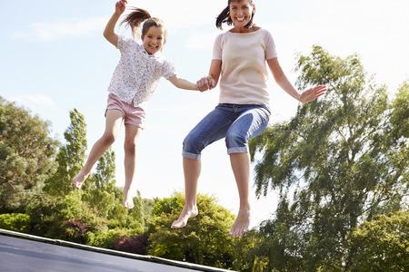 dadã  daughter: Madre e hija que despide en el trampolín Juntos Foto de archivo