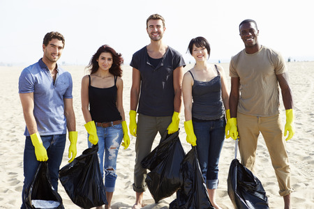 tidying up: Group Of Volunteers Tidying Up Rubbish On Beach