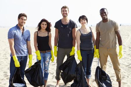 Gruppe von Freiwilligen Aufräumen Rubbish On Beach Standard-Bild