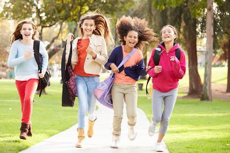 niño con mochila: Grupo de chicas jóvenes corriendo hacia la cámara en el parque Foto de archivo