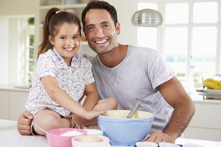 6 years: Father And Daughter Baking Cake In Kitchen
