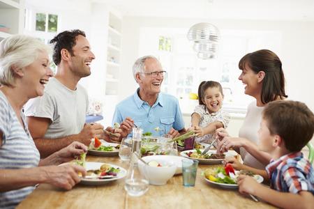 家族: 多世代家族のキッチン テーブルを囲んで食事を食べる