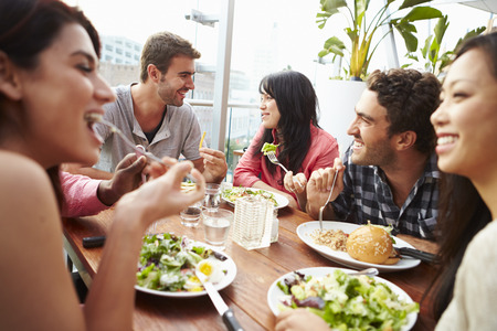 restaurant people: Group Of Friends Enjoying Meal At Rooftop Restaurant