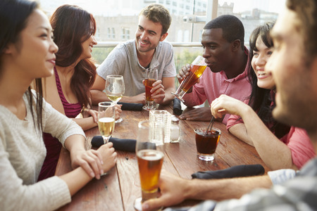 drinks on bar: Group Of Friends Enjoying Drink At Outdoor Rooftop Bar