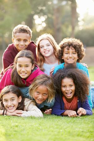 niños jugando en el parque: Grupo de niños tirado en la hierba junto en el Parque