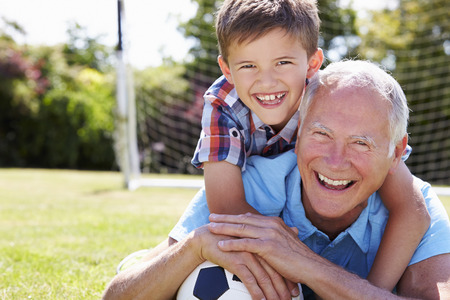 Portrait Of Grandfather And Grandson With Football Stockfoto