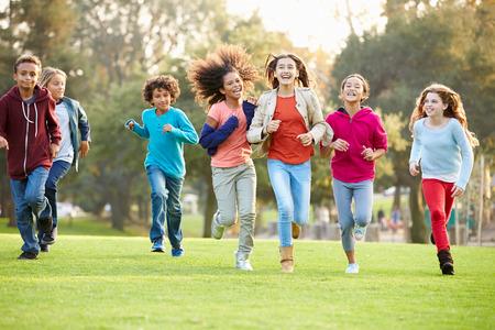niño corriendo: Grupo de niños jovenes corriendo hacia la cámara en el parque Foto de archivo