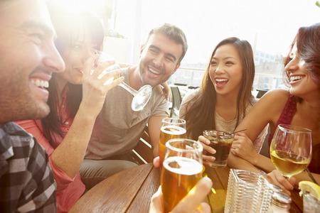 bebiendo vino: Grupo de amigos que disfrutan de la bebida Al aire libre en la azotea Bar Foto de archivo