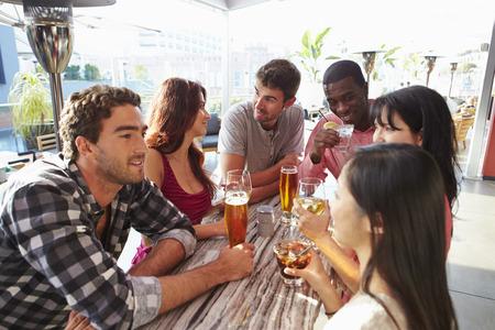 personas hablando: Grupo de amigos que disfrutan de la bebida Al aire libre en la azotea Bar Foto de archivo