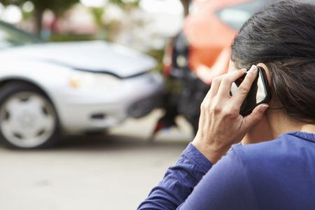 交通事故後の携帯電話をかける女性ドライバー 写真素材
