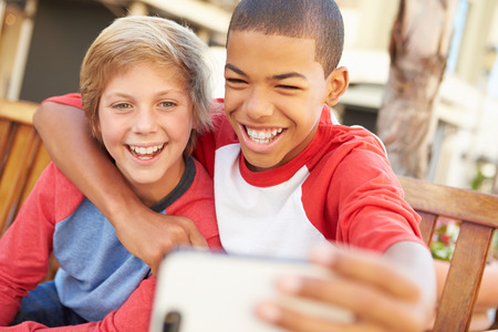 two friends talking: Two Boys Sitting On Bench In Mall Taking Selfie Stock Photo