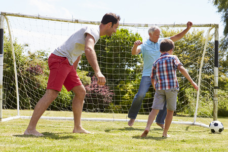 grandfather and grandson: Grandfather, Grandson And Father Playing Football In Garden