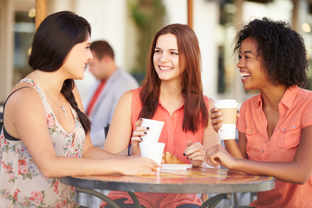 Three Female Friends Meeting In Caf� Фото со стока