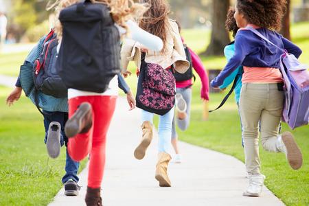 niño con mochila: Vista posterior de los niños ejecutan a lo largo camino en el parque