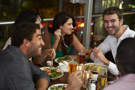 Group Of Friends Enjoying Evening Meal In Restaurant
