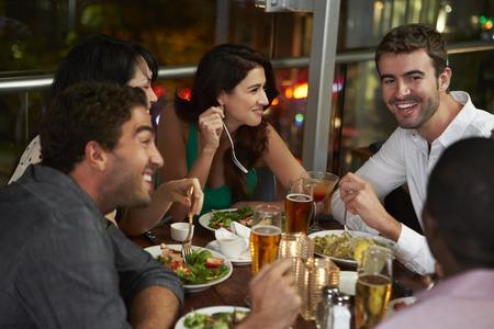 cerveza negra: Grupo de amigos que disfrutan cena en restaurante Foto de archivo