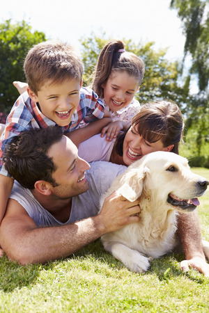 mujer perro: Familia que se relaja en jard�n con perro de mascota Foto de archivo