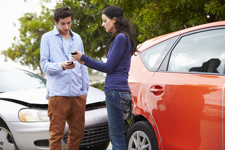 accident damage: Two Drivers Exchange Insurance Details After Accident