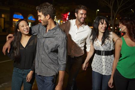 personas caminando: Grupo de amigos que disfrutan Noche Juntos