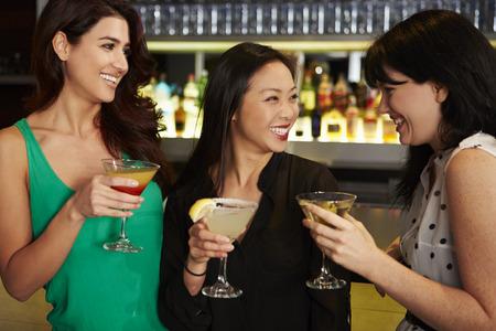 楽しんでいる 3 人の女性友人がカクテル バーで飲む 写真素材