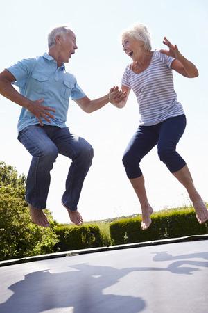 brincando: Pareja mayor rebotar en el trampolín en jardín