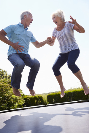 leap: Senior Couple Bouncing On Trampoline In Garden