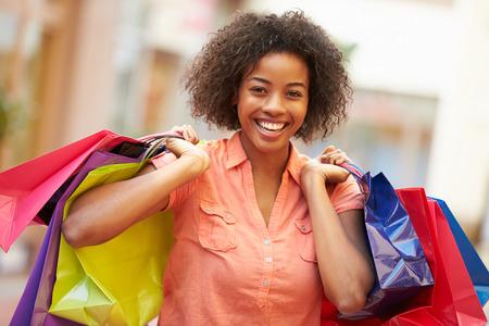 モールのショッピング バッグを持って歩く女性