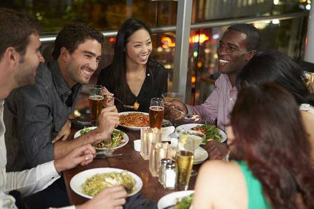 comidas: Grupo de amigos que disfrutan cena en restaurante Foto de archivo