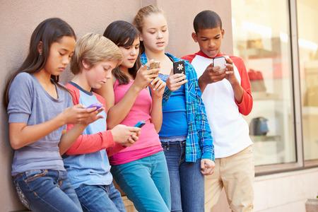 ni�as sonriendo: Grupo de ni�os que se sienta en el centro comercial El uso de tel�fonos m�viles