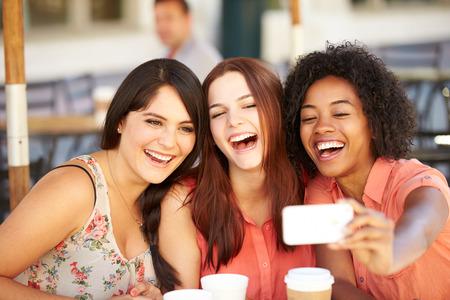riendo: Tres amigos femeninos Tomar selfie En Caf Foto de archivo