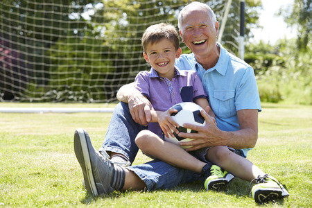 grandson: Grandfather And Grandson Playing Football In Garden