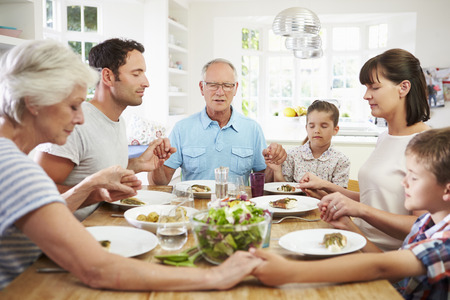 man praying: Multi Generation Family Praying Before Meal At Home