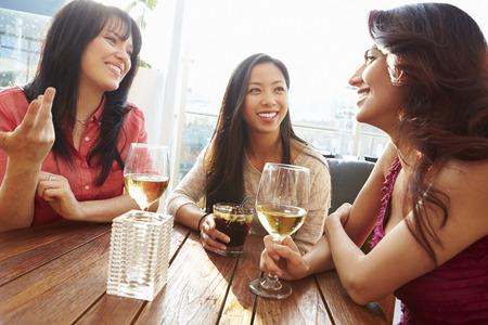tomando vino: Tres amigos femeninos que disfrutan de la bebida en el bar de la azotea al aire libre Foto de archivo
