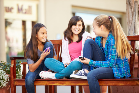 12 13 years: Group Of Girls Sitting In Mall Using Mobile Phones Stock Photo