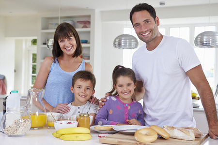 niños desayunando: Familia que hace el desayuno en cocina Juntos Foto de archivo