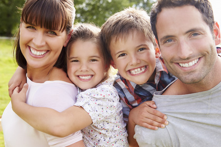 Parents Giving Children Piggybacks Outdoors