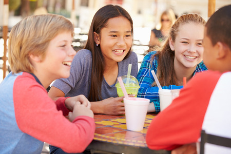 chicas comprando: Grupo de ni�os que cuelgan hacia fuera junto en Caf