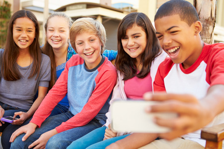 black asian: Group Of Children Sitting On Bench In Mall Taking Selfie Stock Photo