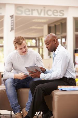 hombres de negro: Estudiante universitario Tener Reunión Con tutor para discutir el trabajo