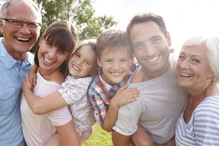 Flergenerationsfamilj ge barnen piggybacks Utomhus