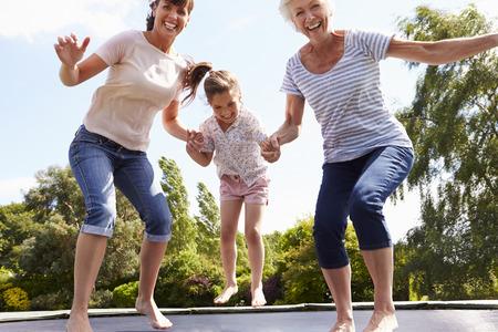 brincando: Abuela, Nieta Y Madre Bouncing en el trampolín