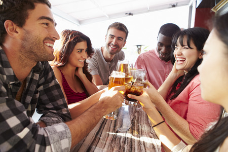 hombre tomando cerveza: Grupo de amigos que disfrutan de la bebida Al aire libre en la azotea Bar Foto de archivo
