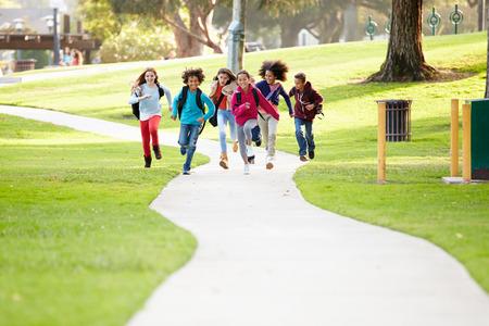 niño con mochila: Grupo de niños que ejecuta a lo largo Camino hacia la cámara en el Parque Foto de archivo