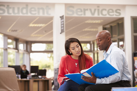 hispanic students: College Student Having Meeting With Tutor To Discuss Work Stock Photo