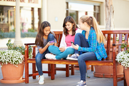 12 13: Group Of Girls Sitting In Mall Using Mobile Phones Stock Photo