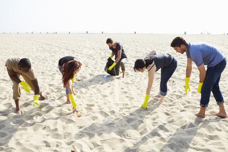 ビーチにゴミを片付けのボランティアのグループ