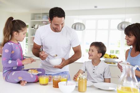niños desayunando: Familia que come el desayuno en cocina Juntos Foto de archivo