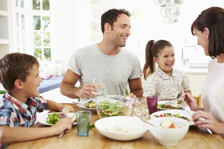 Familia que come la comida alrededor de la mesa de la cocina Juntos