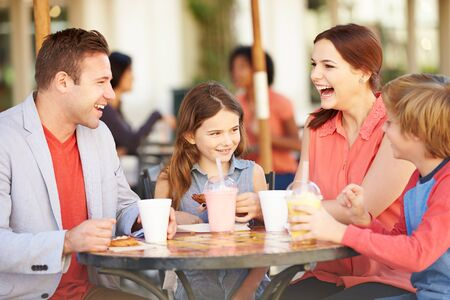 mother and teen daughter: Family Enjoying Snack In Caf� Stock Photo